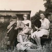 """Anders Johan H-A, Vivi Christiansen, Karen Andersson och Juddi längst fram. Vivis ord: """"Herefter rosinen i pølseenden, billedet er taget hjemme i Brede hvor vi boede som børn, i haven , det er (Elfrida ) onkel Anders kone, der har taget det. Det er min Mor der har hunden på skødet , onkel Anders til venstre, mig med solbriller og min søster Juddi foran."""""""